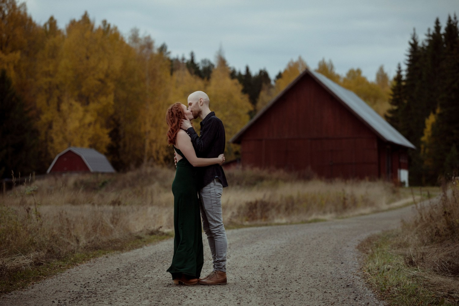 loved up beautiful ginger couple kissing in front of barn