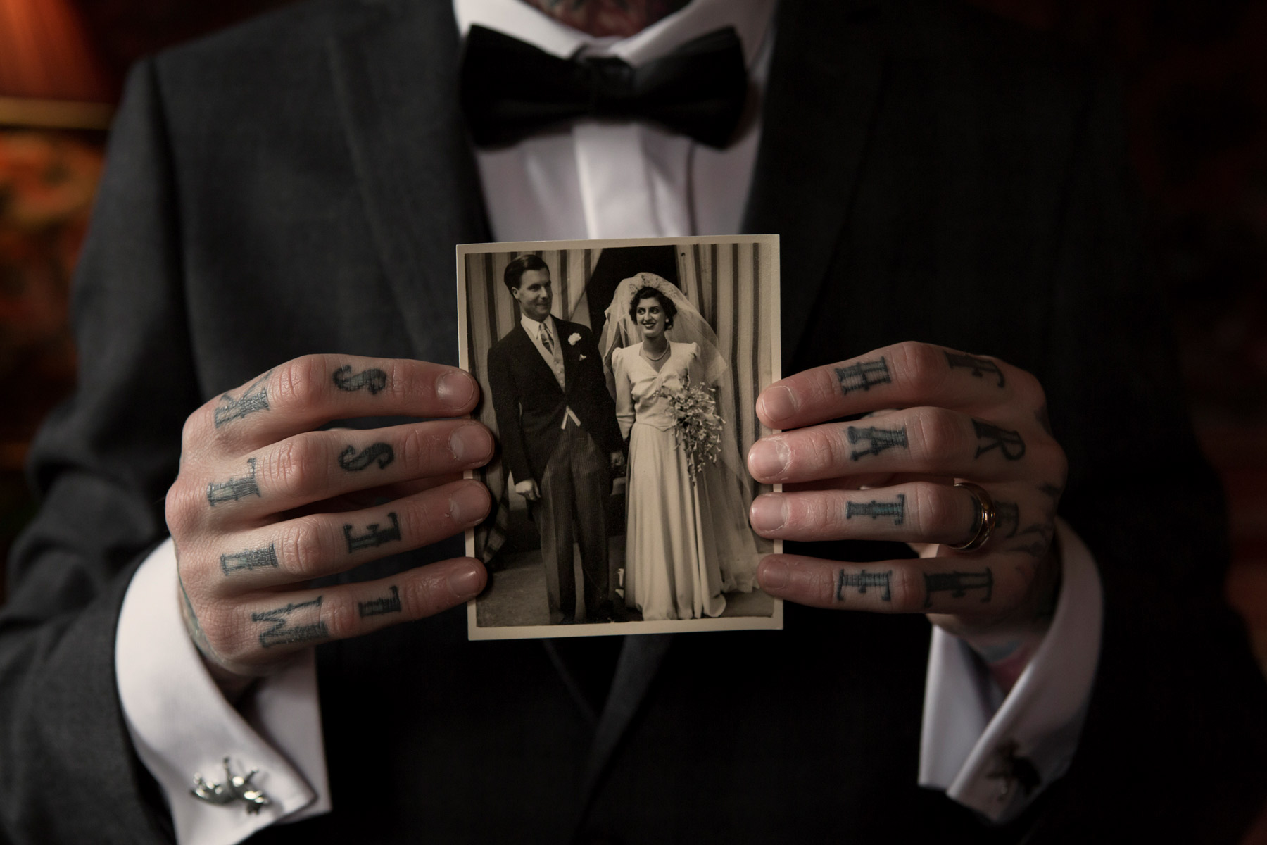 tattooed groom holding picture of relatives at hallowen wedding